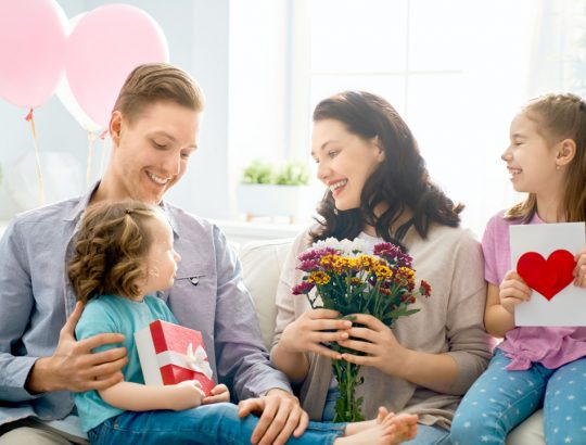 Happy mother's day! Children daughters with dad congratulating mom and give her flowers, gift and card. Family holiday and togetherness.