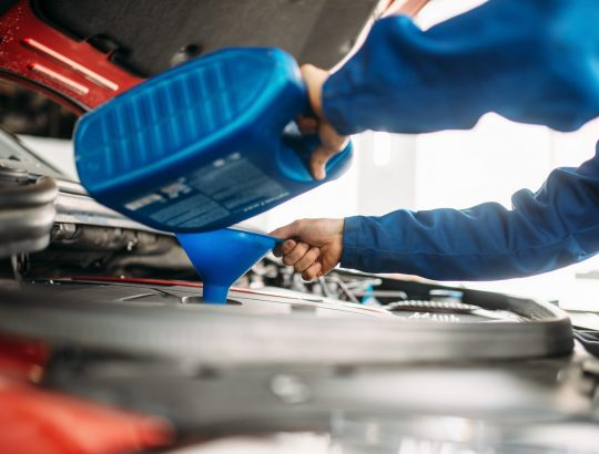 Technician change oil in the car engine. Vehicle motor maintenance, auto-service